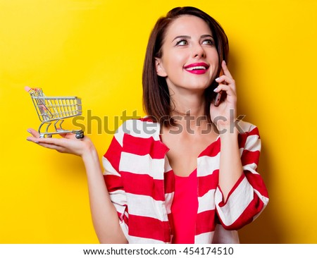 portrait of the beautiful young woman with cart for shopping and mobile phone on the yellow background
