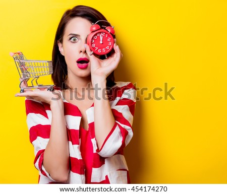 portrait of the beautiful young woman with cart for shopping and red alarm clock on the yellow background