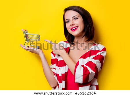 portrait of the beautiful young woman with cart for shopping on the yellow background