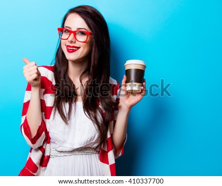 portrait of the beautiful young woman with cup of coffee on the blue background