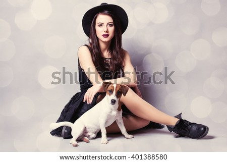 portrait of the beautiful young woman with cute dog on the grey background - stock photo