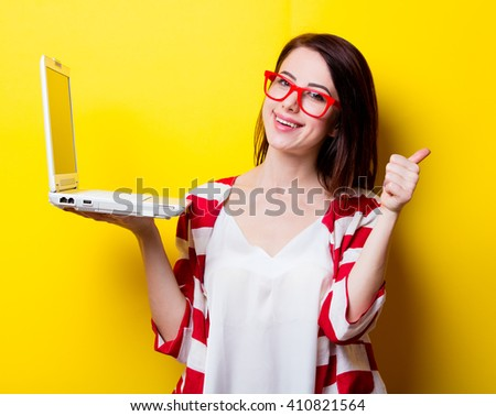 portrait of the beautiful young woman with laptop on the yellow background