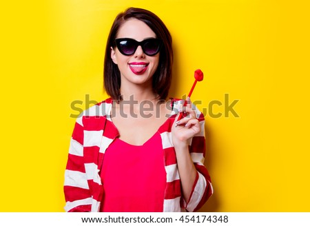 portrait of the beautiful young woman with lip shaped toy on the yellow background