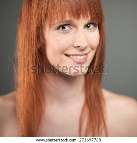 Portrait of the beautiful young woman with red long hair on dark background - stock photo