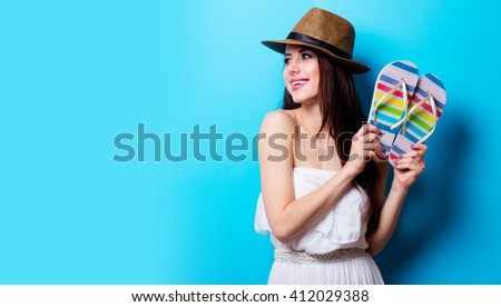 portrait of the beautiful young woman with sandals on the blue background - stock photo