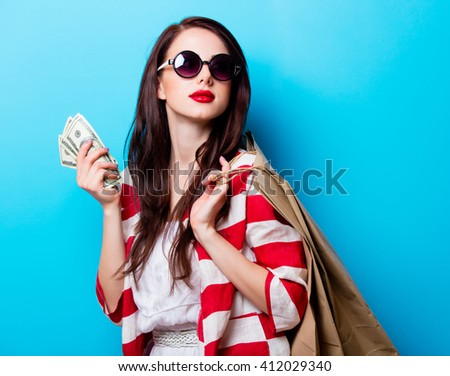 portrait of the beautiful young woman with shopping bags and money on the blue background
