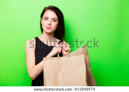 portrait of the beautiful young woman with shopping bags on the green background - stock photo