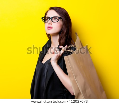 portrait of the beautiful young woman with shopping bags on the yellow background - stock photo