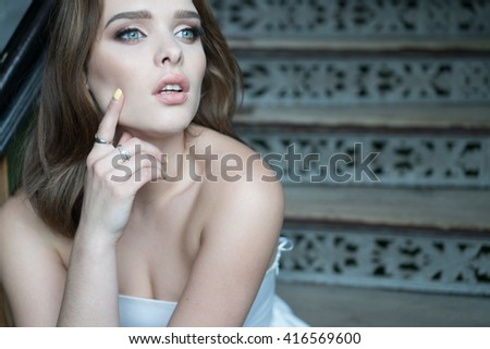 portrait of the beauty woman wearing white dress sitting on the stairs - stock photo