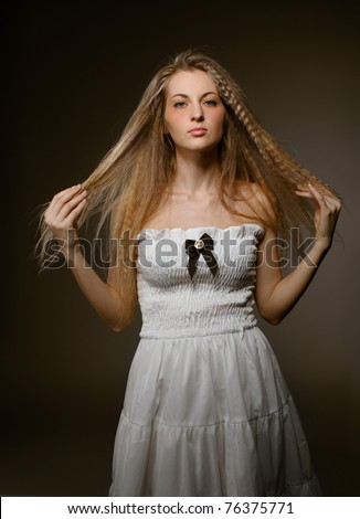 Portrait of the beauty young blond girl in white dress with make up