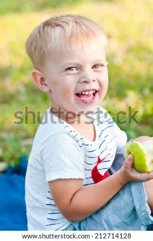 Portrait of the boy eat apple in park - stock photo