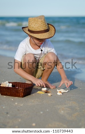 Portrait of the boy in a hat collecting cockleshells on the beach