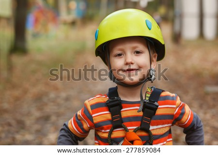 portrait of the brave smiling little boy in a helmet who is cheerfully spending time in park of adventures - stock photo