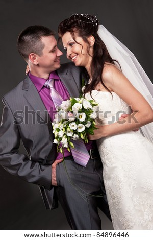 Portrait of the bride and the groom in studio on a grey background - stock photo