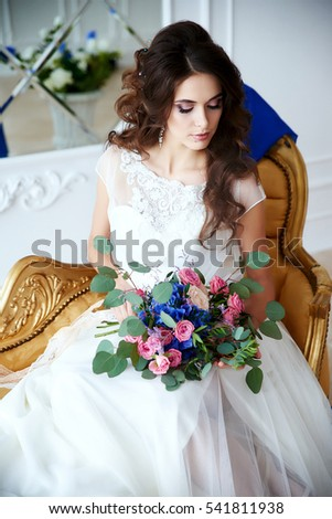 Portrait of the bride in a studio in a wedding dress with a bouquet of flowers in their hands