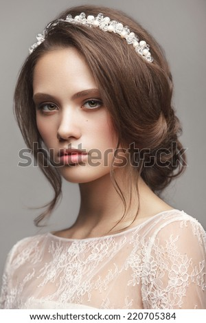 Portrait of the bride with beautiful make up and hairdo on gray background. Wedding trends - stock photo