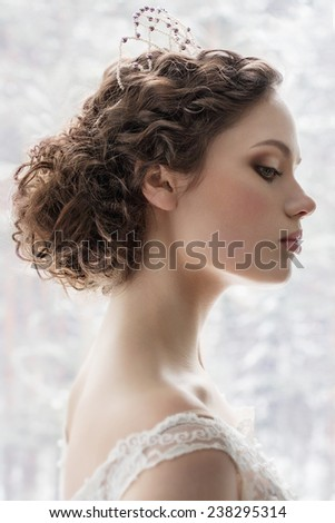 Portrait of the bride with wedding make up and trendy hairdo on white background - stock photo
