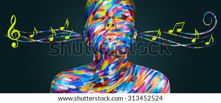 Portrait of the bright beautiful emotional woman with art make-up listen music with notes on dark background - stock photo