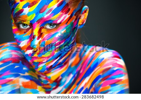 Portrait of the bright beautiful young woman with art make-up on dark background - stock photo