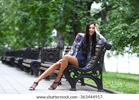 Portrait of the brunette with long hair sitting on a park bench