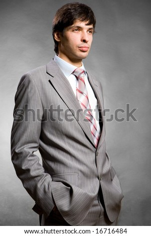 Portrait of the businessman in a grey suit. In studio. - stock photo