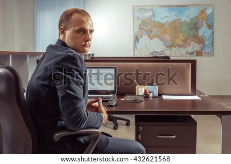Portrait of the caucasian businessman sitting at the table in office.
