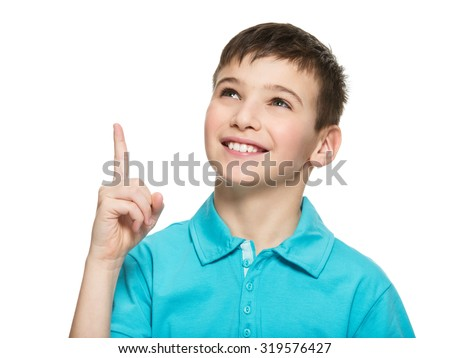Portrait of the cheerful teen boy pointing finger up -  isolated over white background