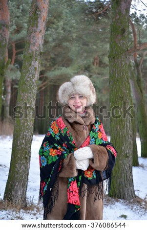 Portrait of the cheerful woman of average years in the winter pine wood