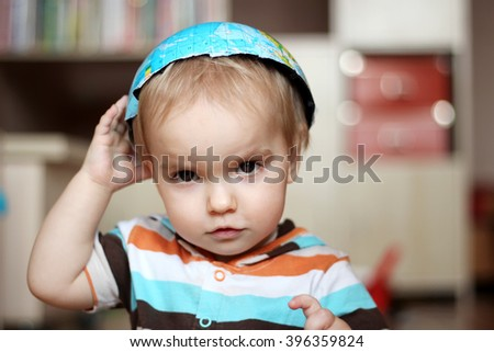 Portrait of the cute boy with the half of the earth globe on his head like a cap, save the earth concept. - stock photo