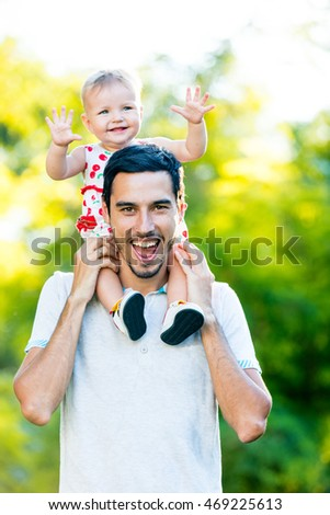portrait of the cute toddler and her father in the park