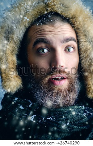 Portrait of the emotional man with beard and mustache dressed in winter clothes, covered with frost.