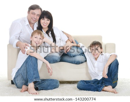 Portrait of the European family of four on a sofa at home