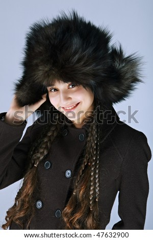 Portrait of the fabulously beautiful girl in big fur cap on a dark background