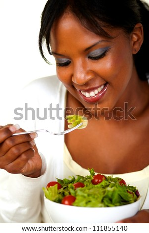 Portrait of the face of a pretty young woman eating green salad on a bowl. - stock photo