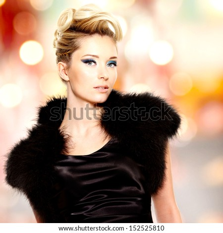 Portrait of the fashion beautiful blond woman with creative  hairstyle posing at studio