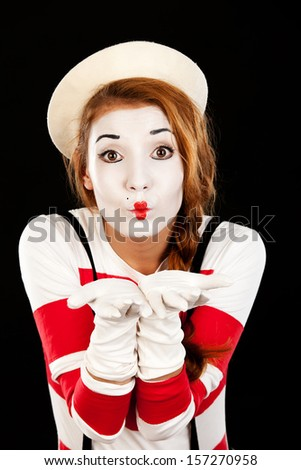 Portrait of the female MIM comedian blows a kiss , isolated on black  background - stock photo