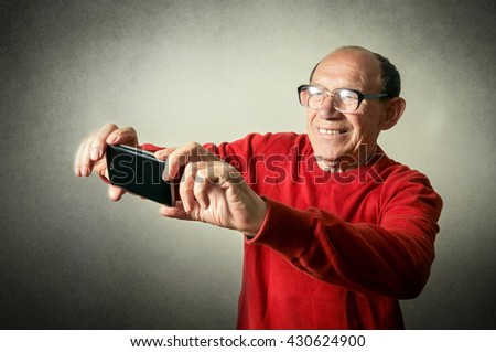 portrait of the funny senior man taking selfie
