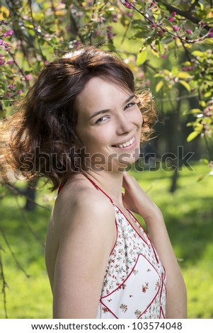 Portrait of the girl against a blossoming apple-tree - stock photo
