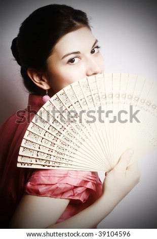 Portrait of the girl in pink to a blouse and a fan in a hand.