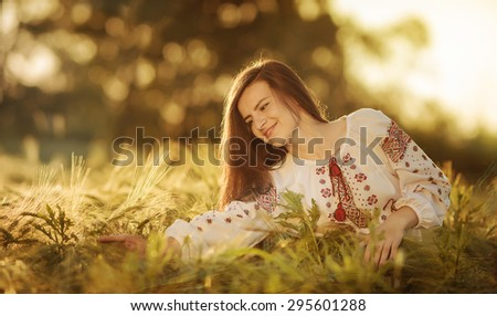 Portrait of the girl in the Ukrainian national clothes in wheat field - stock photo