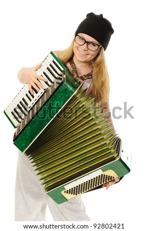 Portrait of the girl, playing an accordion in a cap and glasses