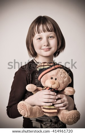 Portrait of the girl - teenager. She is holding a toy teddy bear.