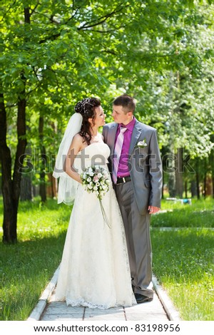 Portrait of the groom and the bride in park in the summer sunny day