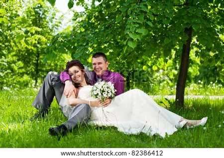 Portrait of the groom and the bride in park on a grass in the summer sunny day - stock photo