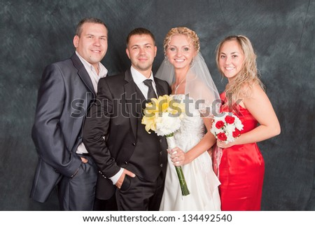 Portrait of the groom, the bride and the best man with the witness in studio - stock photo