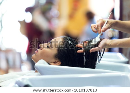 Portrait of the hairdresser applying hair treatment for customer in a beauty salon.