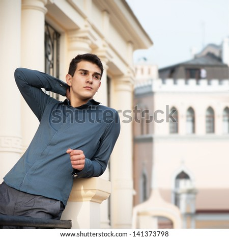 Portrait of the handsome young man in front of the historic building - stock photo