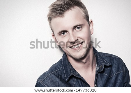 portrait of the handsome young man in jeans clothes on a white background