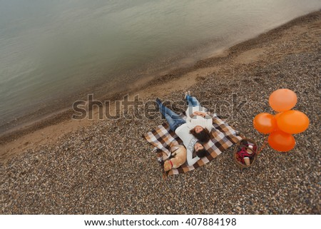 portrait of the happy couple on the beach, river or lake. Cloudy autumn, but they came to the picnic with a dog Labrador puppy. Family happiness, an exemplary family, honeymoon or youth - stock photo
