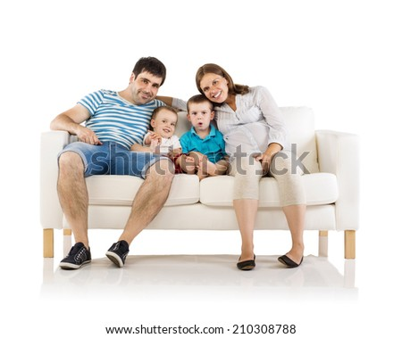 Portrait of the happy family with two children and pregnant mother sitting on sofa, isolated on white background - stock photo